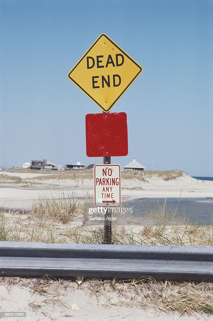 A 'Dead End' sign next to a beach in The Hamptons Long Island USA May 1982