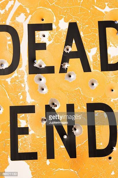 Dead end sign with bullet holes
