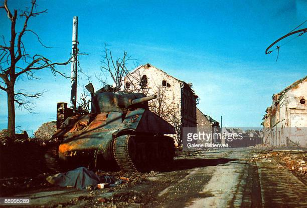 A dead German soldier lying in front of a rusting American Sherman tank Italy 1944