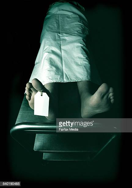 Dead man lying on a trolley in the morgue with toe tag