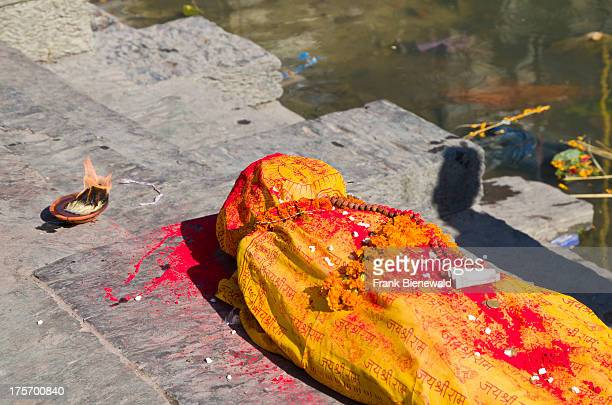 A dead person wrapped in yellow material awaiting its cremation at the burning ghats near Pashupatinath Temple