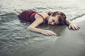 Unconscious young woman lying on the beach.