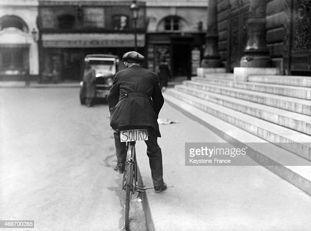 Deaf man on his bike with the word DEAF written on a sign under his saddle in 1928 in Paris France