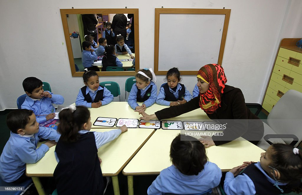 A deaf Palestinian woman teaches hearing impaired children at Atfaluna Society for Deaf Children in Gaza City, on March 7, 2013 on the eve of International Women's Day. International Women's Day is celebrated annually on March 8.