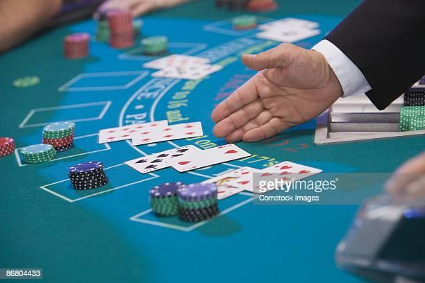 Dealer gesturing at blackjack cards