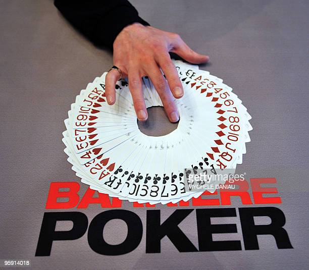 A dealer gives cards to players during the PokerStars European Poker Tour held at the Barriere Casino in Deauville western France on January 20 2010...