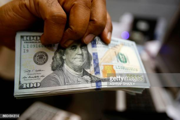 A dealer holds US dollars at a foreign exchange office in central Khartoum on October 12 after the lifting of the US trade embargo came into effect...