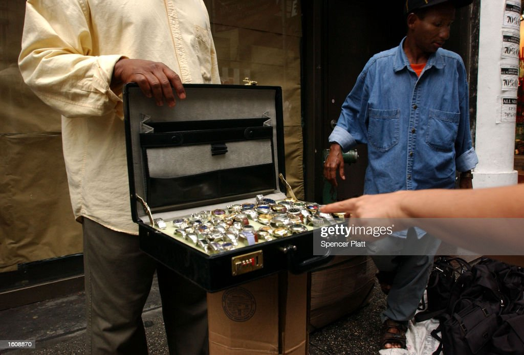 A dealer of counterfeit watches sells his merchandise August 13, 2001 on a street in New York City. Constantly keeping one eye out for the police, these wandering dealers of knock-off CDs, purses, sunglasses, watches and videos can be found by the dozens in any of the tourist districts of New York City.