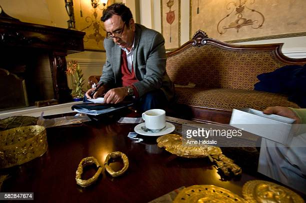 A dealer of preColumbian gold presents his latest acquisitions to tourists in a luxurious hotel in Cuenca southern Ecuador