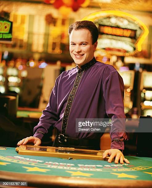 Dealer standing behind poker table in casino, portrait