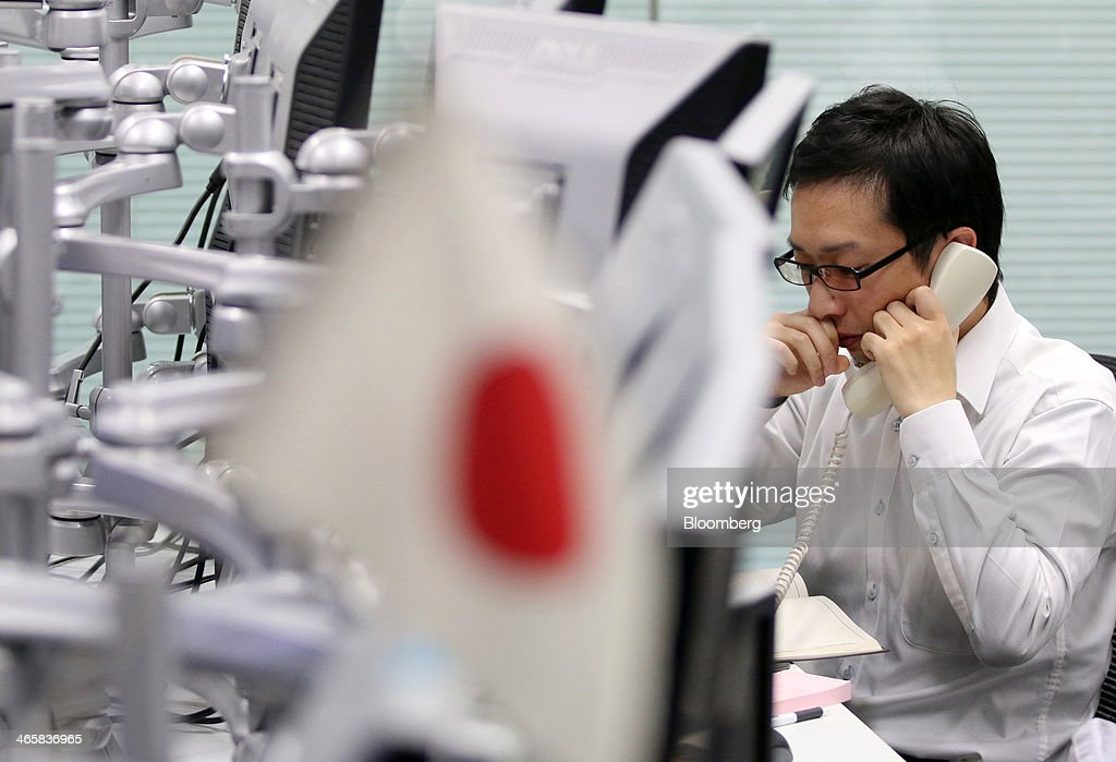 A dealer talks on a phone as a Japanese national flag sits on display at a foreign exchange brokerage in Tokyo, Japan, on Thursday, Jan. 30, 2014. Japanese stocks fell, with the Topix index closing at its lowest in six weeks, after the yen gained as the Federal Reserve pushed ahead with stimulus cuts amid turmoil in emerging markets. Photographer: Yuriko Nakao/Bloomberg via Getty Images