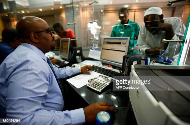 A dealer works at a foreign exchange office in central Khartoum on October 12 after the lifting of the US trade embargo came into effect Sudan's...