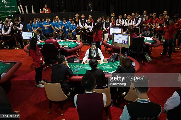 Dealers compete at baccarat tables during the All Asia Dealers' Championship at the Global Gaming Expo inside the Venetian Macau resort and casino...