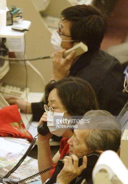 Dealers on the floor of the Hong Kong Stock Exchange wear masks to protect against a deadly pneumonia virus 01 April 2003 that has killed 15 people...