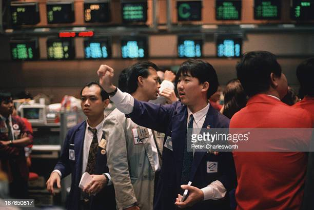Dealers trade currencies on the floor of SIMEX the Singapore International Monetary Exchange