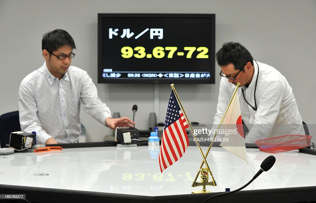 Dealers trade in front of an electronic board flashing the numbers of the foreign exchange rate of the yen against one US dollar (top) at a foreign exchange brokerage in Tokyo on February 6, 2013.