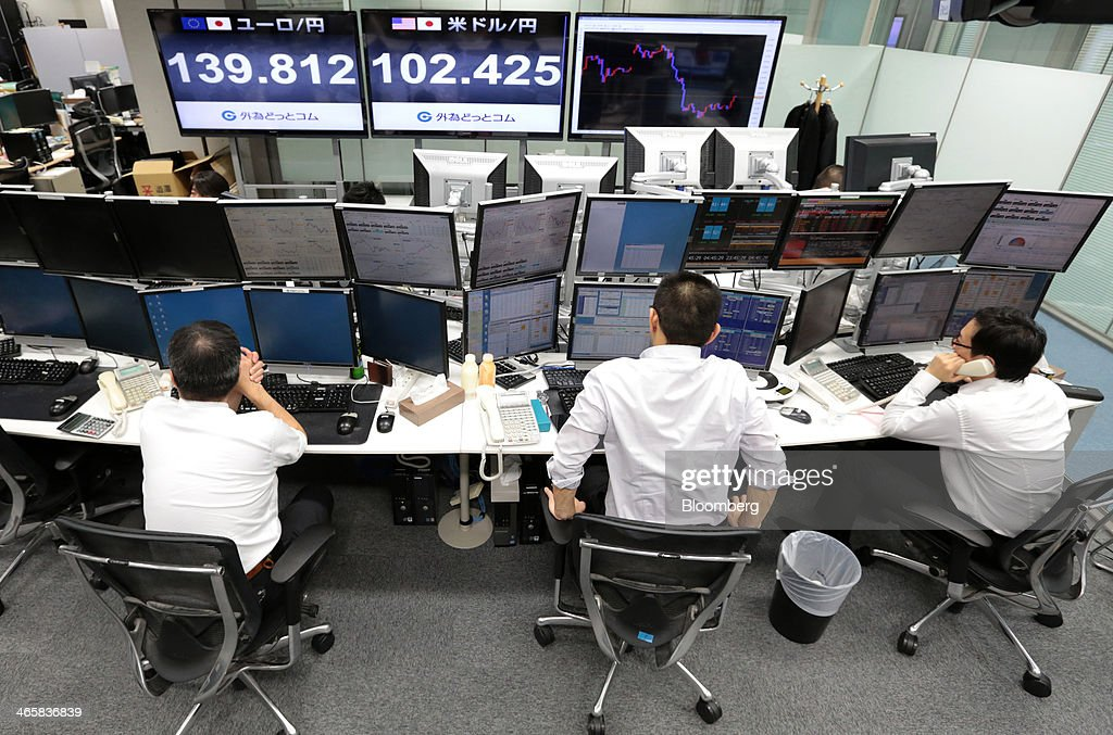 Dealers work at a foreign exchange brokerage in Tokyo, Japan, on Thursday, Jan. 30, 2014. Japanese stocks fell, with the Topix index closing at its lowest in six weeks, after the yen gained as the Federal Reserve pushed ahead with stimulus cuts amid turmoil in emerging markets. Photographer: Yuriko Nakao/Bloomberg via Getty Images
