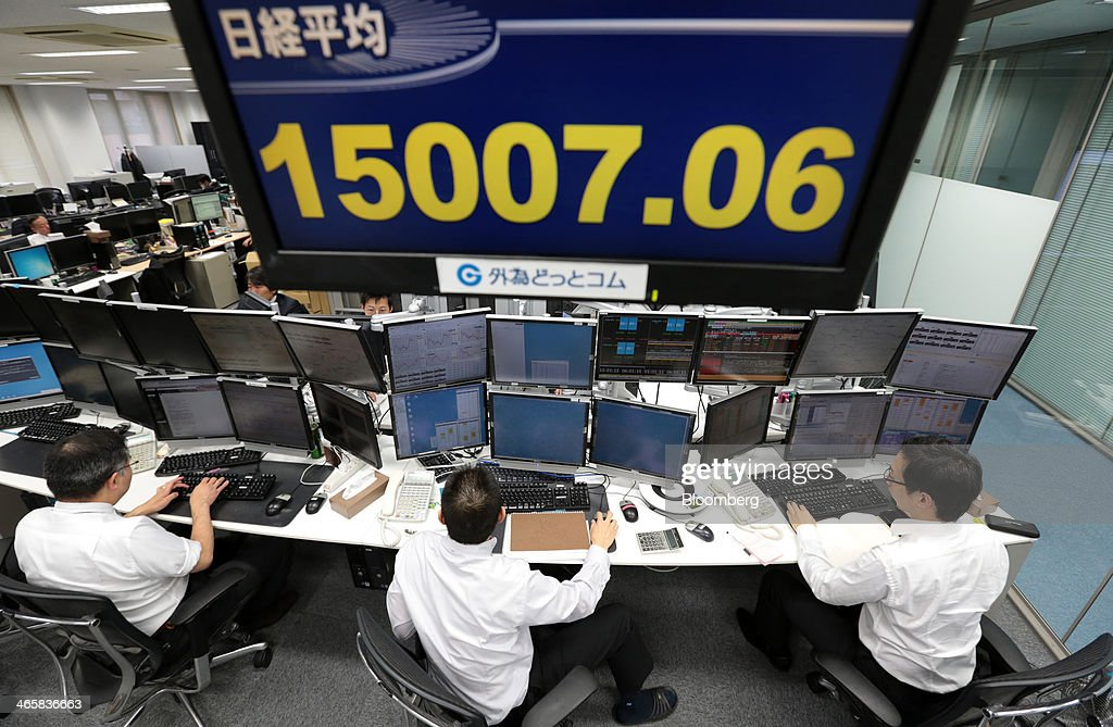 Dealers work under a monitor flashing the closing price of the the Nikkei Stock Average at a foreign exchange brokerage in Tokyo, Japan, on Thursday, Jan. 30, 2014. Japanese stocks fell, with the Topix index closing at its lowest in six weeks, after the yen gained as the Federal Reserve pushed ahead with stimulus cuts amid turmoil in emerging markets. Photographer: Yuriko Nakao/Bloomberg via Getty Images