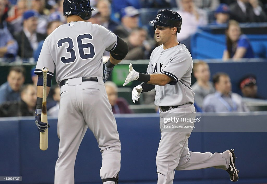 Dean Anna #45 of the New York Yankees is congratulated by <a gi-track='captionPersonalityLinkClicked' href=/galleries/search?phrase=Carlos+Beltran&family=editorial&specificpeople=167108 ng-click='$event.stopPropagation()'>Carlos Beltran</a> #36 after scoring a run in the eighth inning during MLB game action against the Toronto Blue Jays on April 4, 2014 at Rogers Centre in Toronto, Ontario, Canada.
