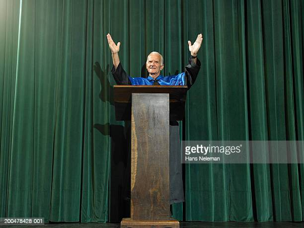 Dean at lectern raising arms
