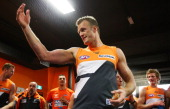 Dean Brogan of the Giants celebrates with team mates after they won the round 19 AFL match between the Greater Western Sydney Giants and Port...