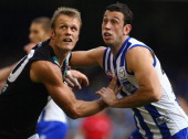 Dean Brogan of the Power and Todd Goldstein of the Kangaroos challenge eacother for the ball during the round six AFL match between the North...