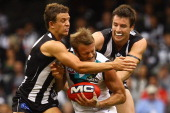 Dean Brogan of the Power is tackled by Luke Ball and Darren Jolly of the Magpies during the round one AFL match between the Collingwood Magpies and...
