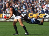 Dean Brogan of the Power is tackled by Travis Varcoe of the Cats during the round three AFL match between the Geelong Cats and the Port Adelaide...