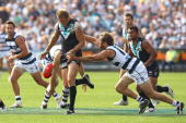 Dean Brogan of the Power kicks whilst being tackled by Joel Corey of the Cats during the round four AFL match between the Geelong Cats and the Port...