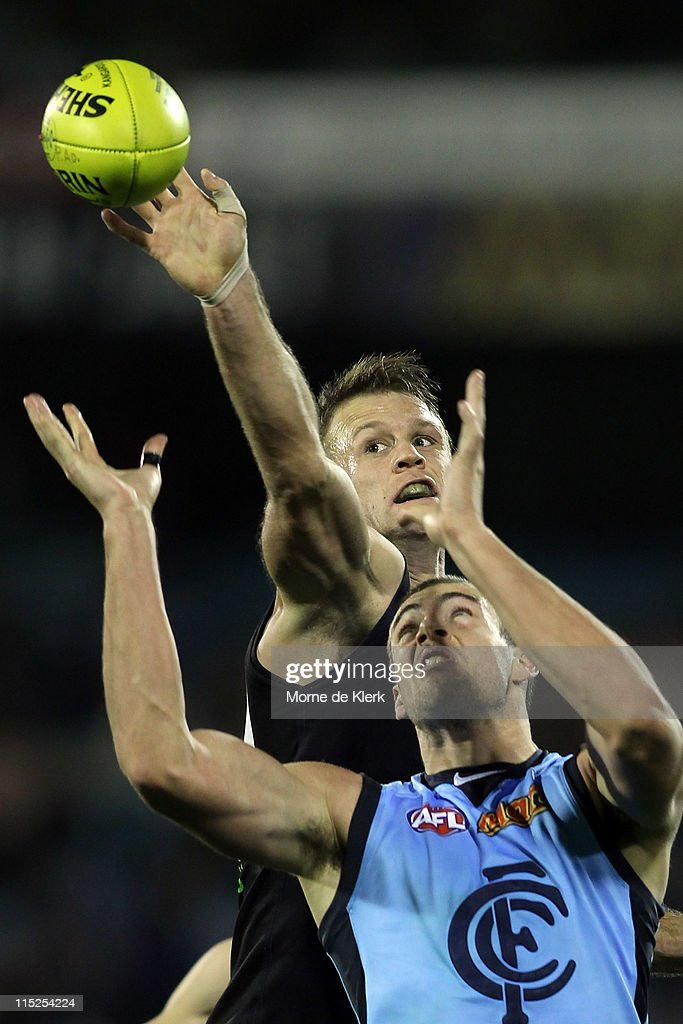 Dean Brogan of the Power spoils the ball through the arms of Shaun Hampson of the Blues during the round 11 AFL match between the Port Adelaide Power...
