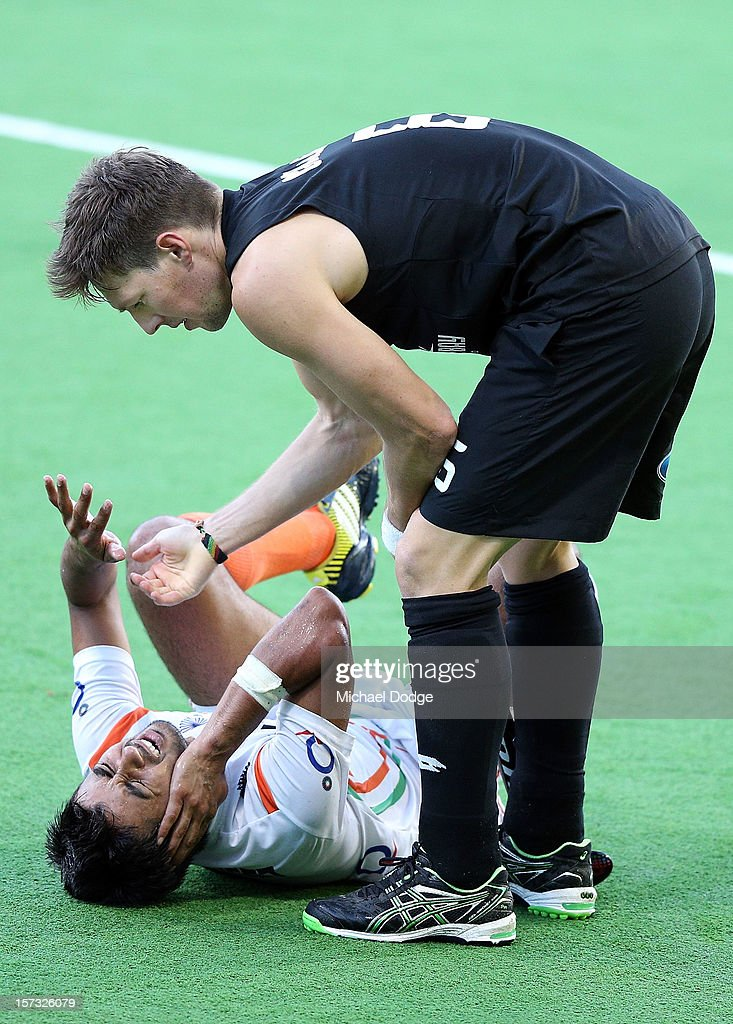 Dean Couzins of New Zealand tries to comfort Manpreet Singh (L) of India after he was hit in the head by a hockey stick during the match between India and New Zealand during day two of the Champions Trophy on December 2, 2012 in Melbourne, Australia.