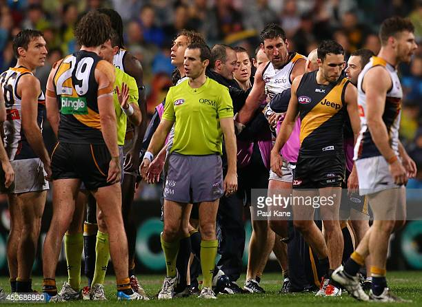 Dean Cox of the Eagles is assisted from the field by trainers as umpires Dean Margetts and Jeff Dalgleish talk with Tyrone Vickery of the Tigers of...