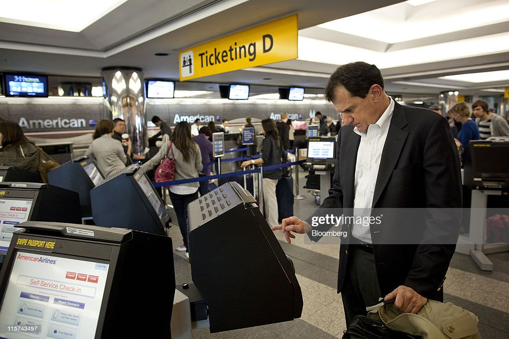 Dean Douglas an American Airlines Inc passenger attempts to check himself in from a selfservice checkin kiosk at LaGuardia Airport in the Queens...