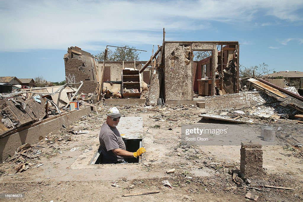 Dean Dye looks over a storm shelter in a home that was destroyed by a tornado on May 22, 2013 in Moore, Oklahoma. The shelter is across the street from Dye's daughter's home which was also damaged by the tornado. The tornado of at least EF4 strength and two miles wide touched down May 20 killing at least 24 people and leaving behind extensive damage to homes and businesses. U.S. President Barack Obama promised federal aid to supplement state and local recovery efforts.