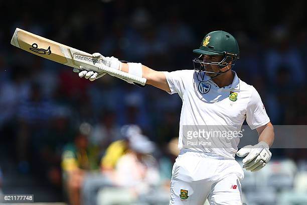 Dean Elgar of South Africa raises his bat to the players rooms after reaching his half century during day three of the First Test match between...