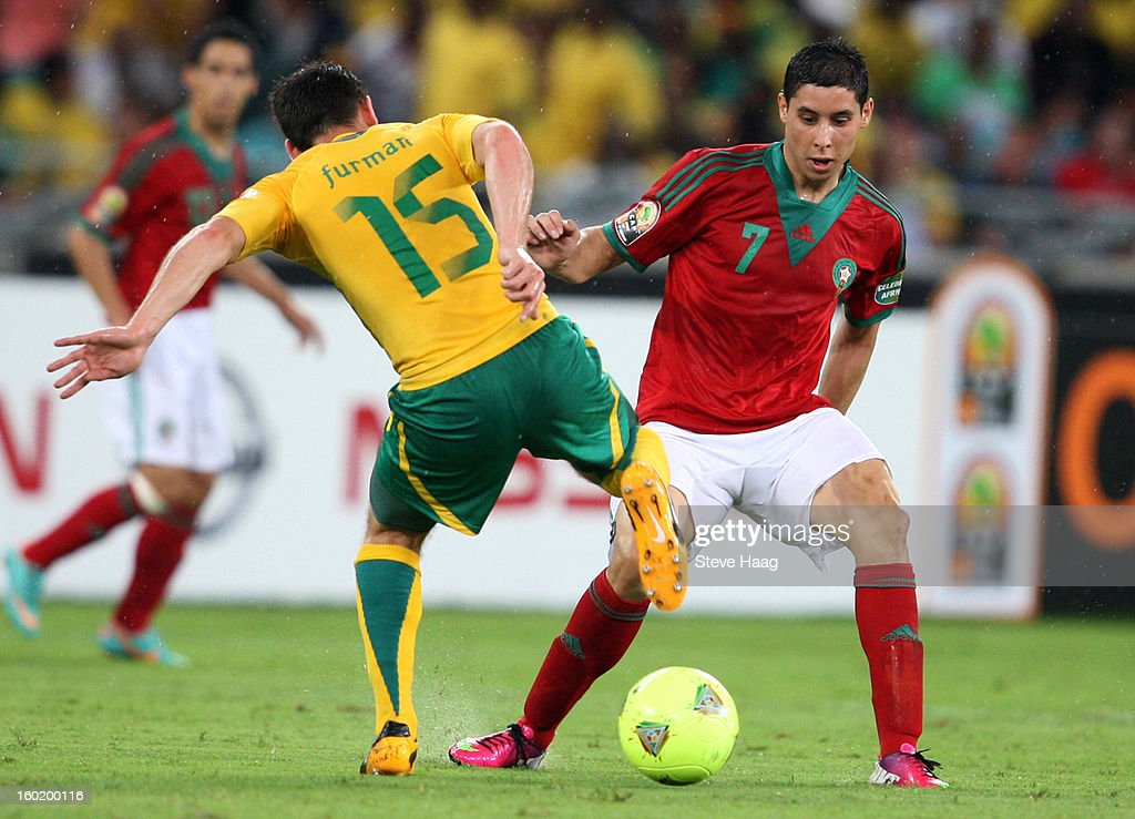 Dean Furman of South Africa looks to tackle Abdelaziz Barrada of Morocco during the 2013 African Cup of Nations match between Morocco and South Africa at Moses Mahbida Stadium on January 27, 2013 in Durban, South Africa.