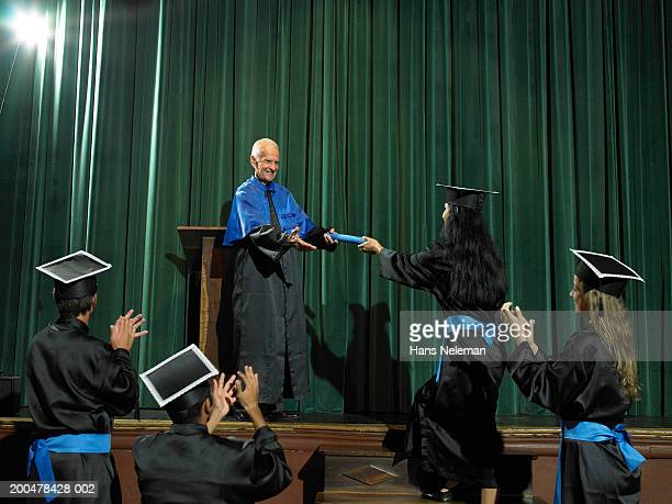 Dean handing out diploma, graduates applauding