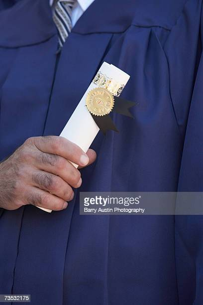 Dean holding diploma, close-up