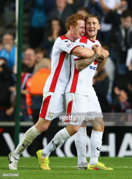 Dean Lewington of Milton Keynes Dons celebrates his team's 40 victory with Kyle McFadzean after the Capital One Cup Second Round match between MK...