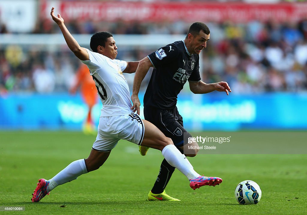 Dean Marney of Burnley is challenged by Jefferson Montero of Swansea City during the Barclays Premier League match between Swansea City and Burnley at Liberty Stadium on August 23, 2014 in Swansea, Wales.