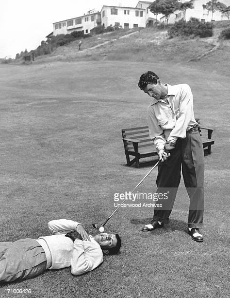 Dean Martin appears to be ready to drive off a tee that Jerry Lewis is fearfully holding in his mouth California 1953