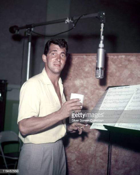 Dean Martin US actor and singer holding a cup and smoking a cigarette while standing before a sheet music stand and a microiphone in a recording...