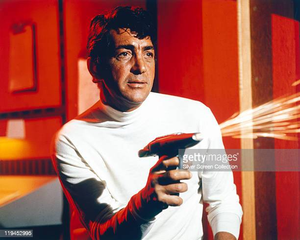 Dean Martin US actor and singer wearing a white polo neck jumper and firing a gun from which sparks fly in a publicity image issued for the film...