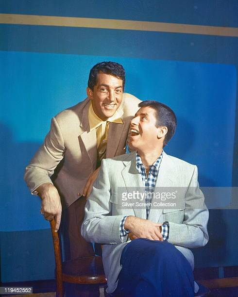 Dean Martin US actor and singer with US actor and comedian Jerry Lewis sitting on a chair in a studio portrait against a blue background circa 1950