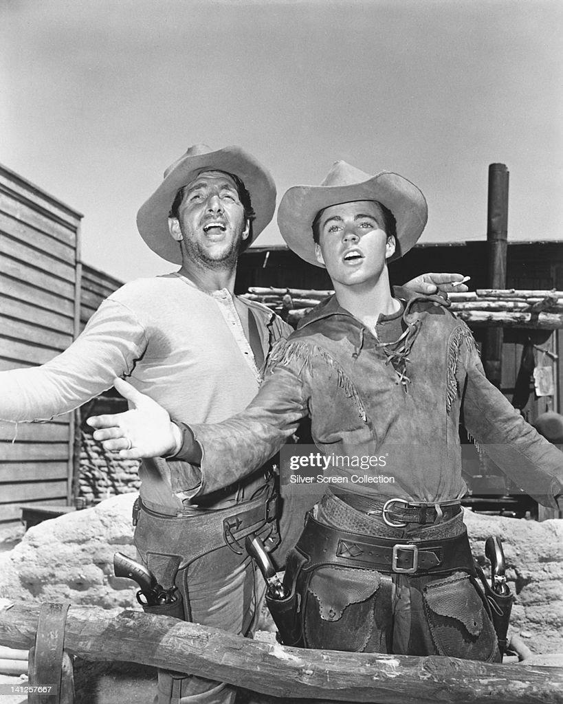 Dean Martin (1917-1995), US singer and actor, and Ricky Nelson (1940-1985), US singer and actor, singing on set of the film 'Rio Bravo', USA, 1959. The Western, directed by Howard Hawks (1896-1977), starred Martin as 'Dude', and Nelson as 'Colorado Ryan'.