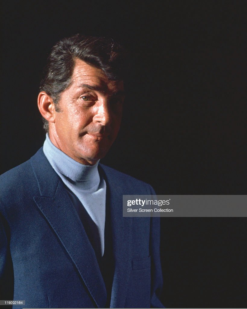 Dean Martin (1917-1995), US singer and actor, wearing a dark blue jacket and light blue polo neck jumper, against a black background, in a publicity portrait issued for the film, 'The Silencers', USA, 1966. The spy spoof, directed by Phil Karlson (1908-1985), starred Martin as 'Matt Helm'.