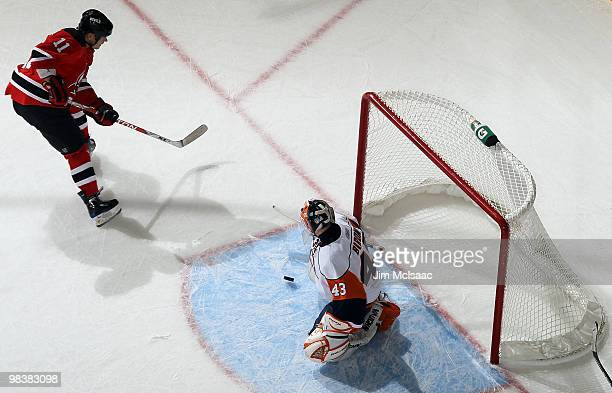 Dean McAmmond of the New Jersey Devils is stopped in the first period by Martin Biron of the New York Islanders at the Prudential Center on April 10...