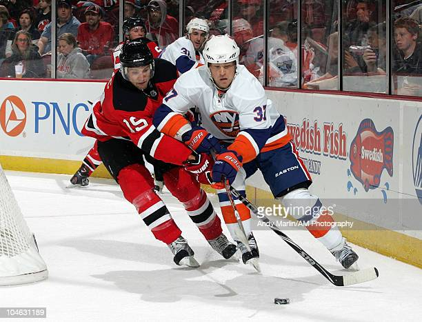 Dean McAmmond of the New York Islanders and Travis Zajac of the New Jersey Devils battle hard for a loose puck during their preseason game at the...