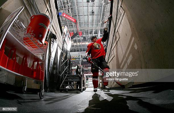 Dean McAmmond of the Ottawa Senators reaches out to a fan as he walks down the players' tunnel prior to a game against the Boston Bruins at...