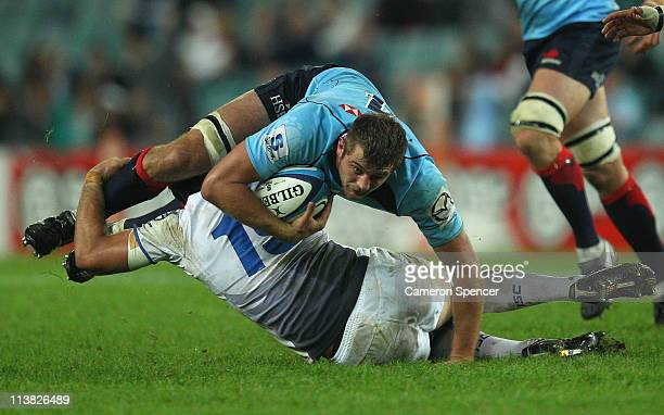 Dean Mumm of the Waratahs is tackled during the round 12 Super Rugby match between the Waratahs and the Western Force at the Sydney Football Stadium...